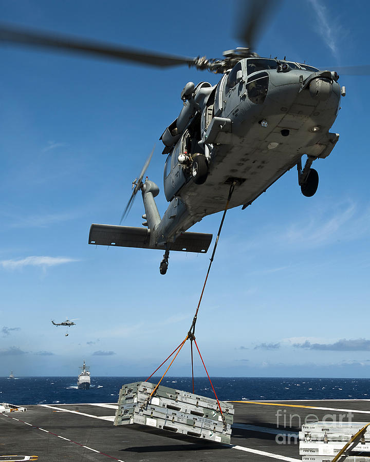 Flight Deck Photograph - An Mh-60s Sea Hawk Helicopter Lowers by Stocktrek Images