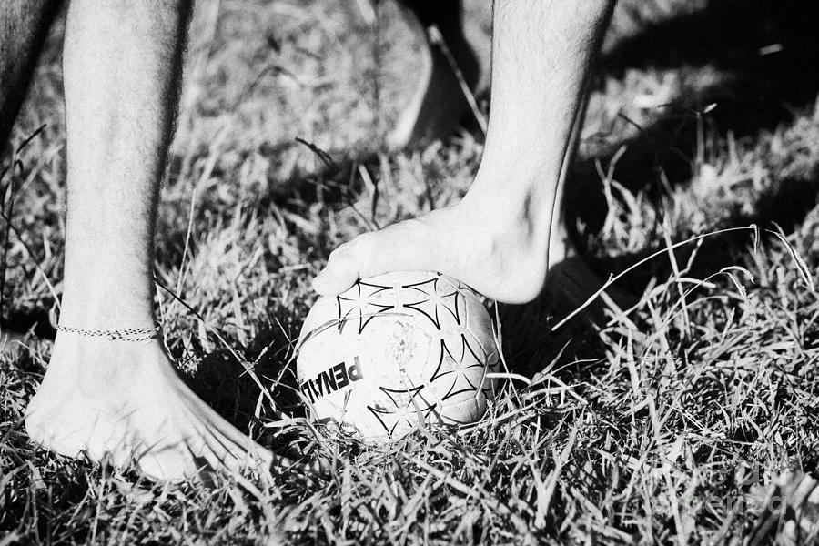 Men Photograph - Argentinian Hispanic Men Start A Football Game Barefoot In The Park On Grass by Joe Fox