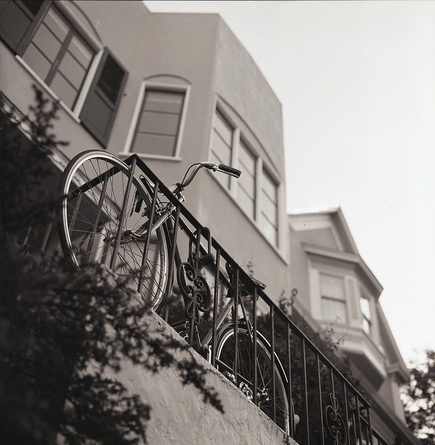 Vertical Photograph - Bike Locked On Fence Against House by Copyright Ricky G. Brown 2011