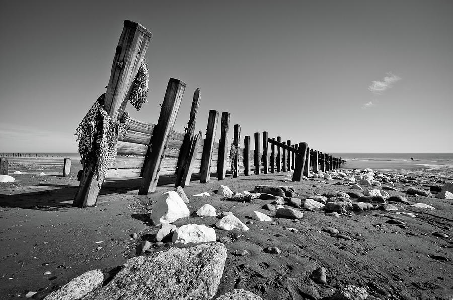 Horizontal photograph black and white beach with rocks and wood by billy richards photography