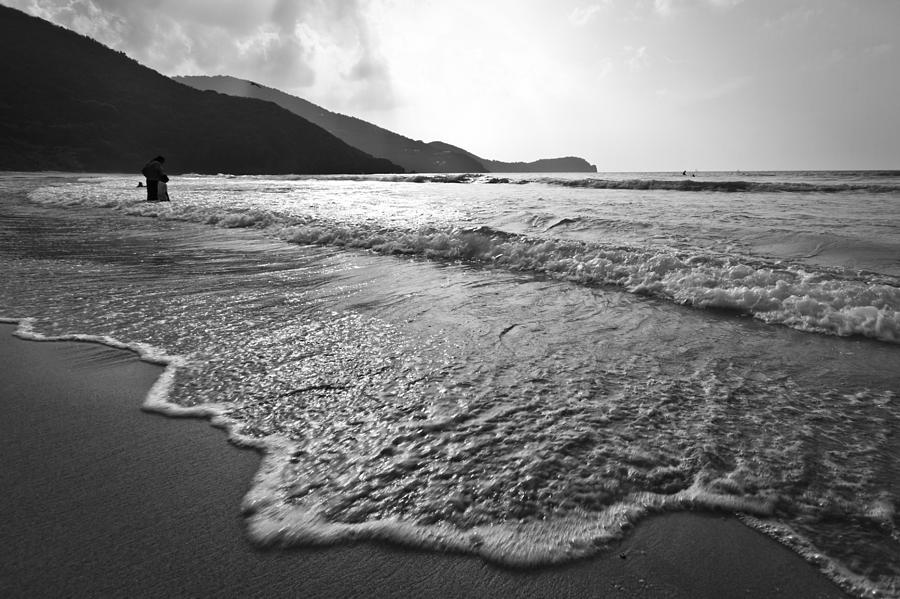 Black And White Image Of Waves Rolling Onto A Beach Photograph
