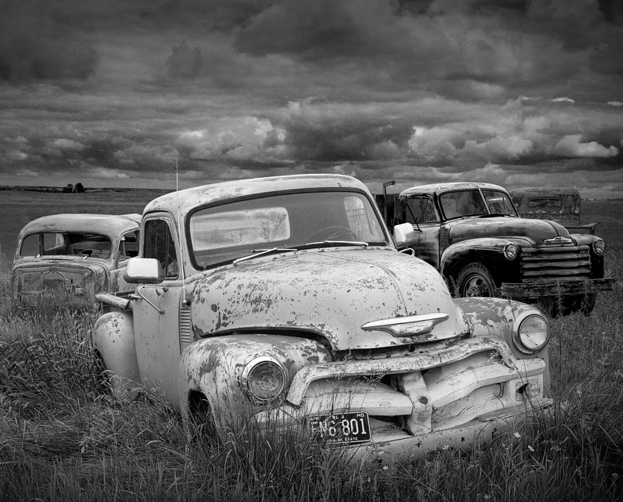 Landscape photograph black and white photograph of a junk yard with vintage auto bodies by