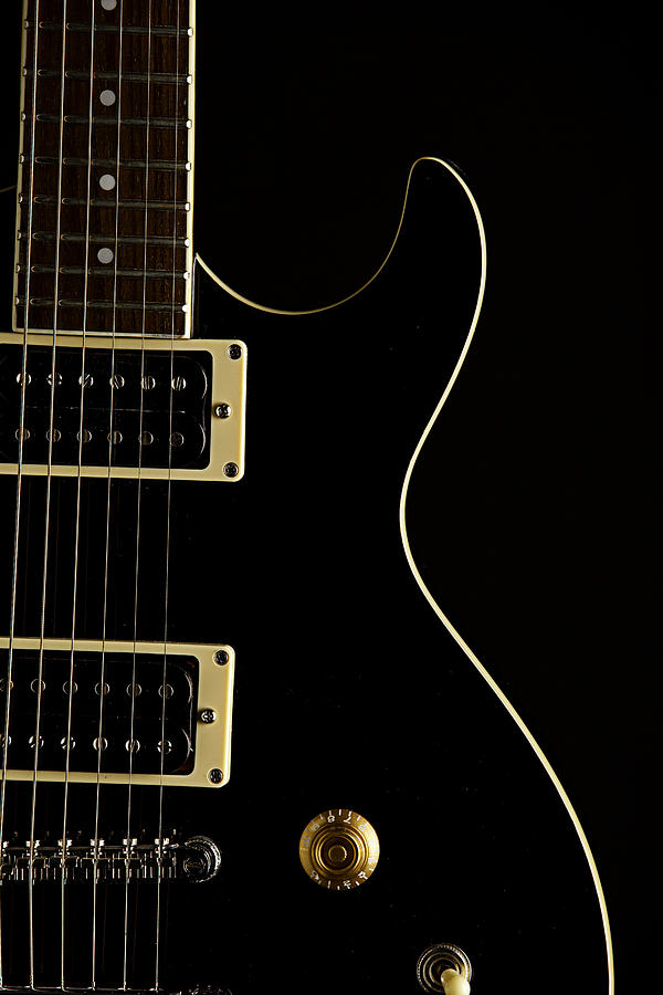 black electric guitar on dark background photograph by m k