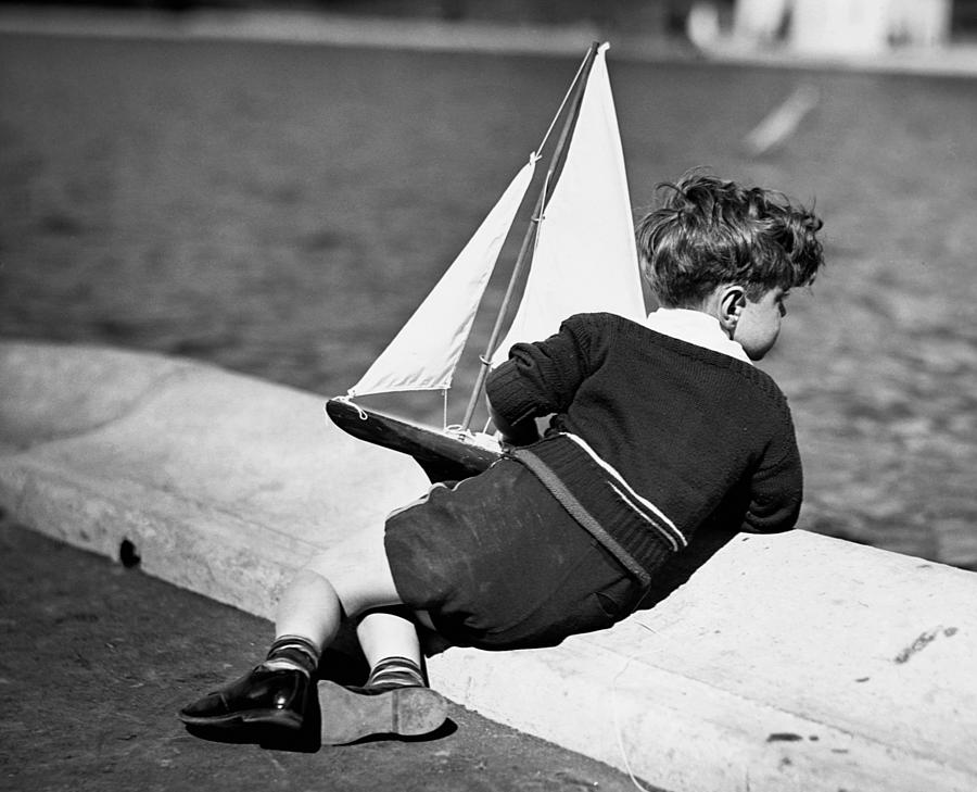 Child Photograph - Boy Playing With Toy Sailboat by George Marks