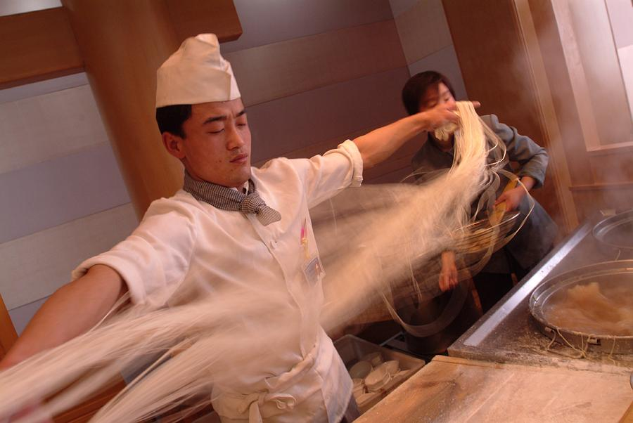 Asia Photograph - Chef Stretches Dough As He Makes Fresh by Richard Nowitz