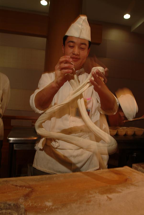 Asia Photograph - Chef Twirls Dough As He Makes Fresh by Richard Nowitz