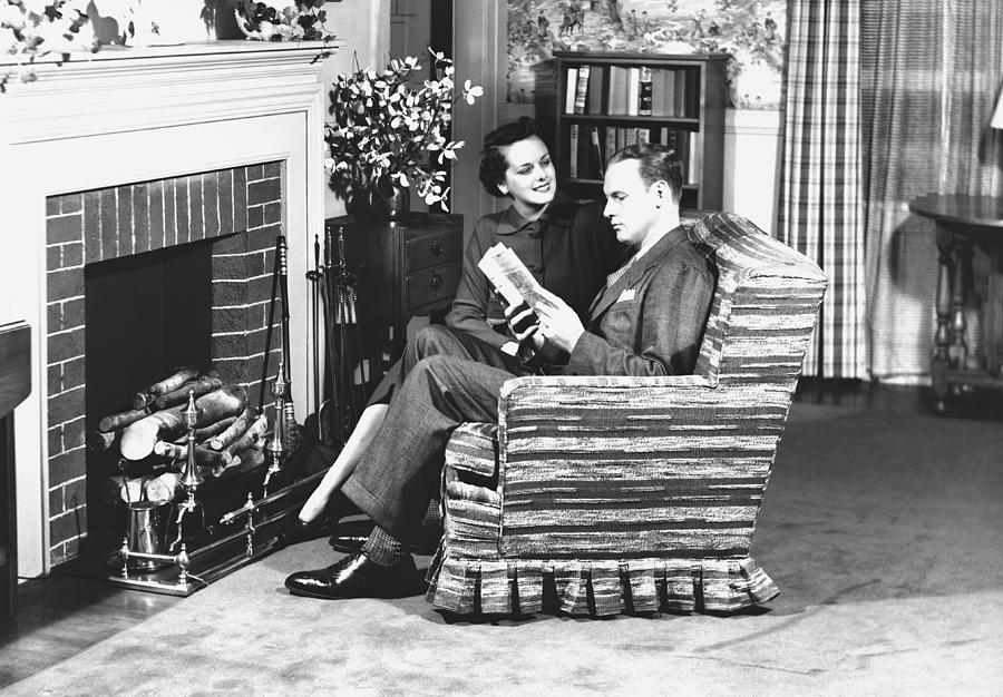 Adult Photograph - Couple Sitting On Armchair In Front Of Fireplace, (b&w) by George Marks