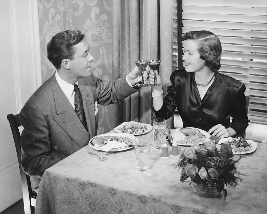 Adult Photograph - Couple Toasting At Dinner Table, (b&w), Elevated View by George Marks