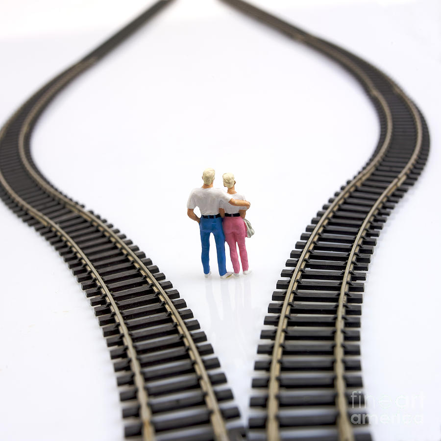 Unfocused Photograph - Couple Two Figurines Between Two Tracks Leading Into Different Directions Symbolic Image For Making Decisions by Bernard Jaubert