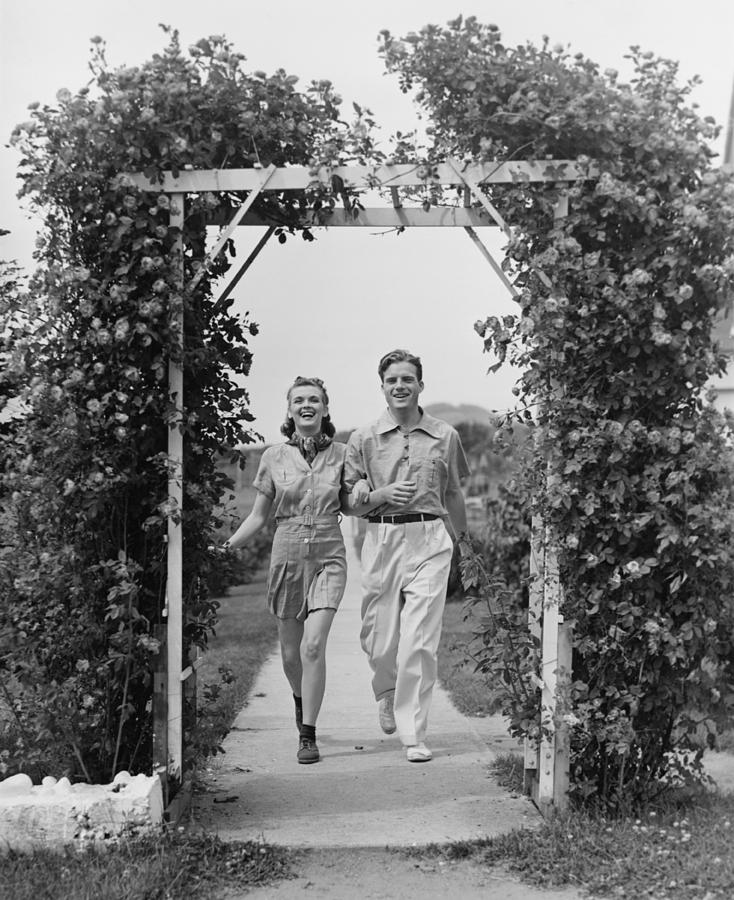 Adult Photograph - Couple Walking On Footpath Towards Rose Covered Pergola, (b&w) by George Marks