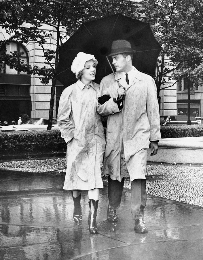 Adult Photograph - Couple W/umbrella Walking In The Rain by George Marks