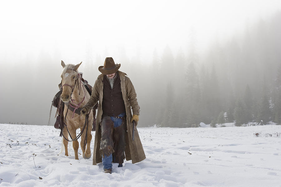Adult Photograph - Cowboy Walking His Horse And Holding A Shotgun by Thomas Kokta
