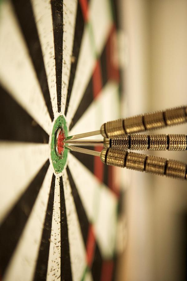 Darts In Bulls-eye Of Target Photograph by Thinkstock