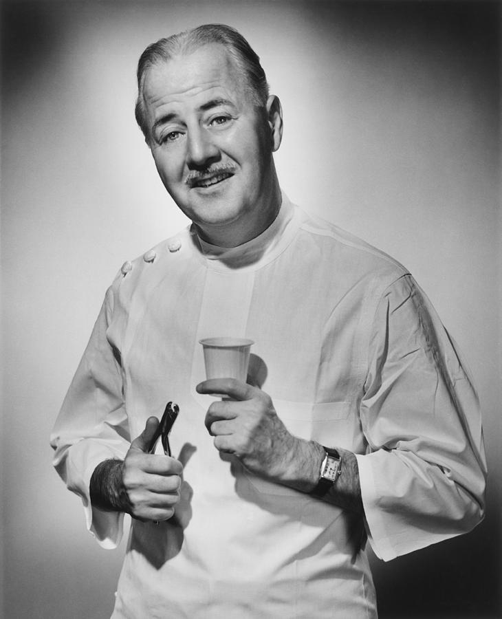 Adult Photograph - Dentist Holding Pliers And Cup Posing In Studio, (b&w), Portrait by George Marks