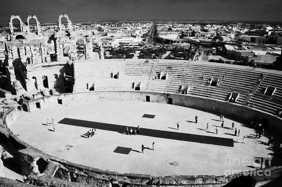 Tunisia Photograph - distant straight roman road leading through el Djem towards tourists the old roman colloseum arena by Joe Fox