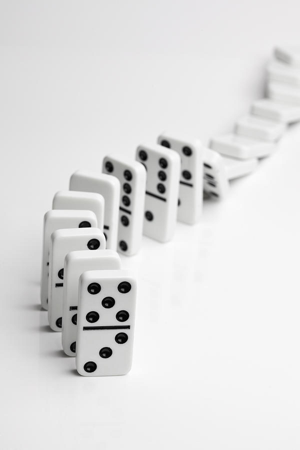 Vertical Photograph - Dominoes Falling Over In A Chain Reaction by Larry Washburn