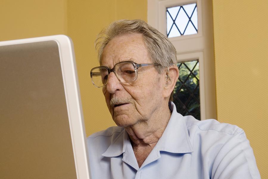 Laptop Photograph - Elderly Man Using A Laptop Computer by Steve Horrell