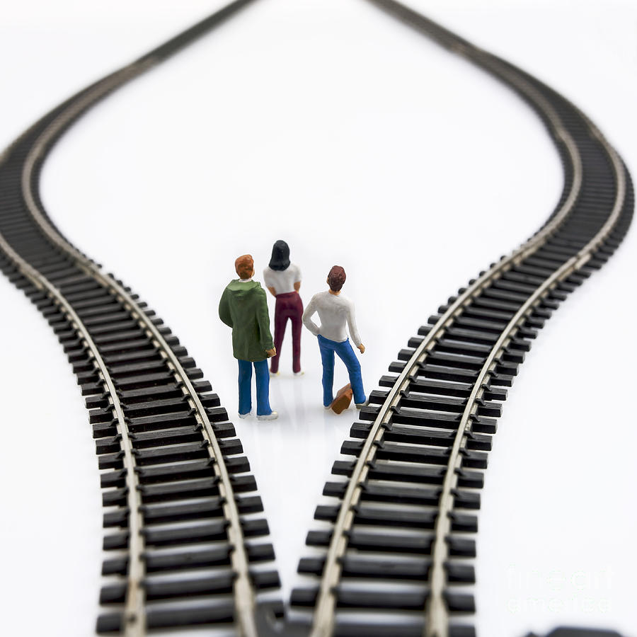 Reflective Photograph - Figurines Between Two Tracks Leading Into Different Directions Symbolic Image For Making Decisions. by Bernard Jaubert