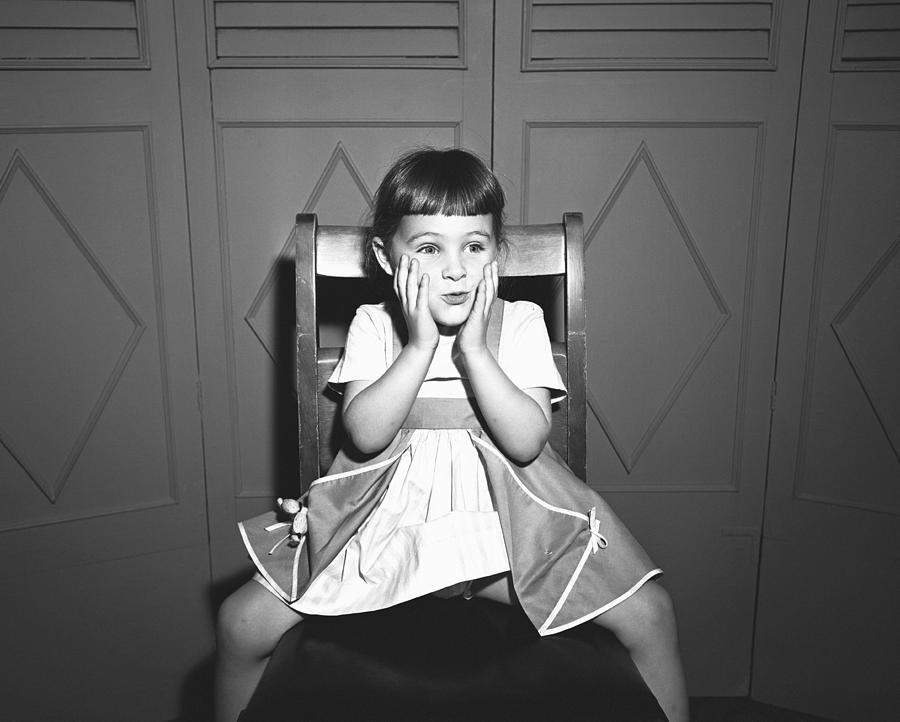 Child Photograph - Girl (5-5) Sitting Astride Chair, Making Face, (b&w), by George Marks