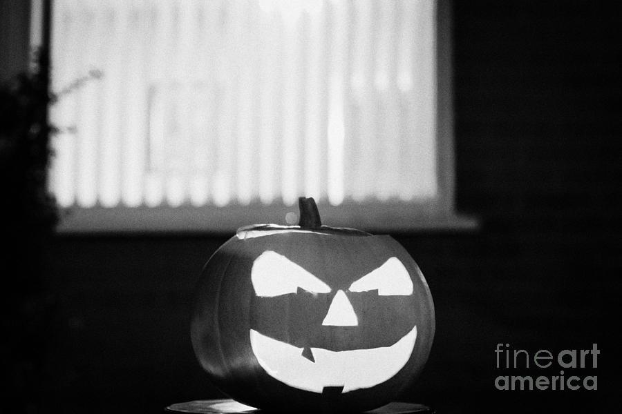 Halloween Photograph - Illuminated Halloween Pumpkin Jack-o-lantern Outside The Window Of A House To Ward Off Evil Spirits  by Joe Fox