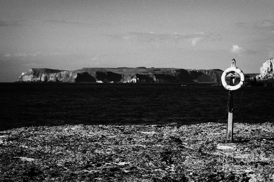 Life Photograph - Lifebelt On Rocks At Ballintoy With Moyle Sea And Rathlin Island by Joe Fox