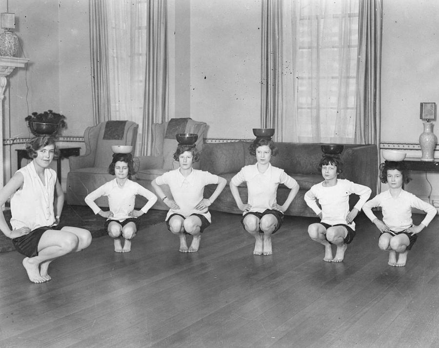 Horizontal Photograph - Line Of Girls (7-12) Exercising With Bowls On Heads (b&w) by Hulton Archive