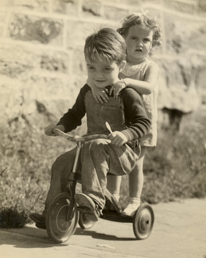 Child Photograph - Little Boy Giving Little Girl Ride On Tricycle by George Marks