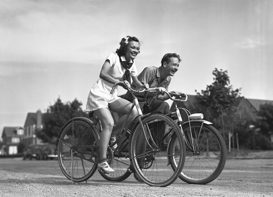 Adult Photograph - Man And Woman Riding Bicycles, (b&w), by George Marks