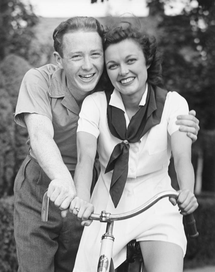 Adult Photograph - Man Embracing Woman Sitting On Bike, (b&w), Portrait by George Marks