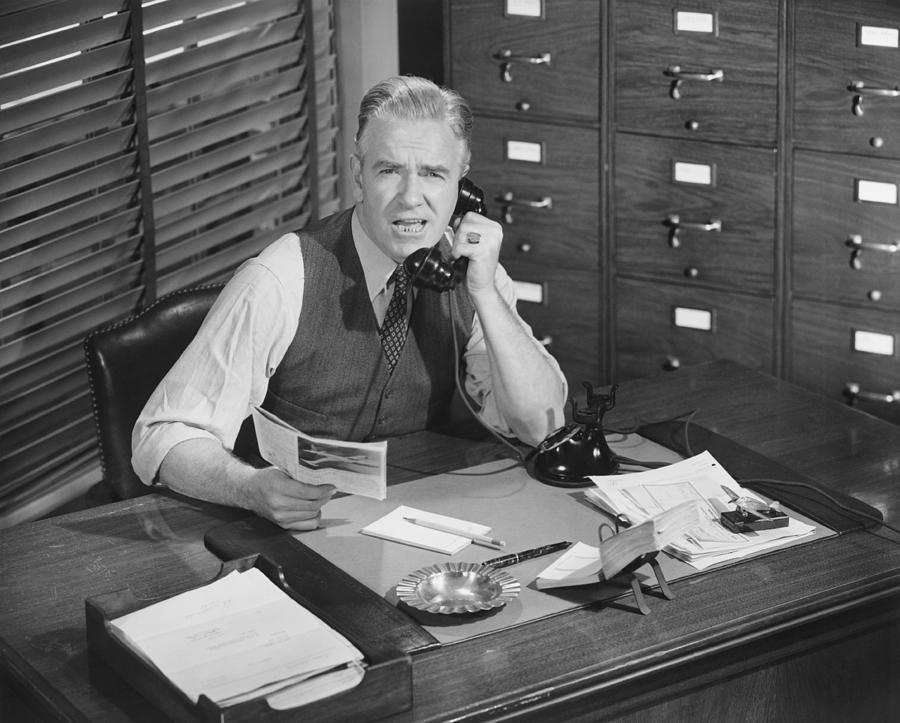 Adult Photograph - Man Sitting At Desk, Talking On Phone, (b&w), Elevated View by George Marks