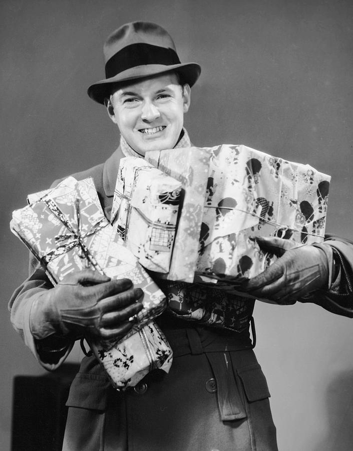 Adult Photograph - Man With Coat, Gloves And Hat Carrying Christmas Gifts by George Marks