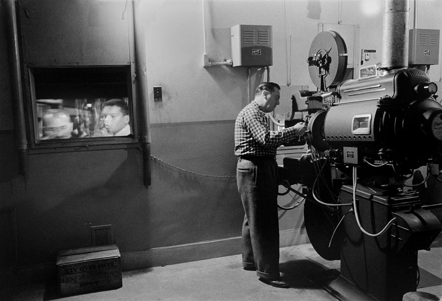 1950s Candids Photograph - Man Working A Projector In A Movie by Everett