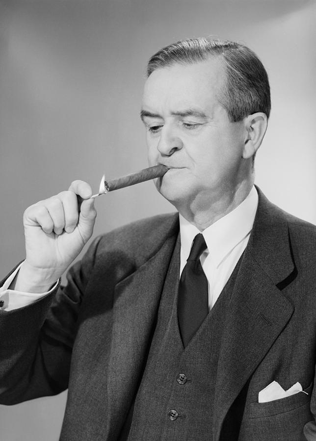 Adult Photograph - Mature Man Lighting Cigar by George Marks