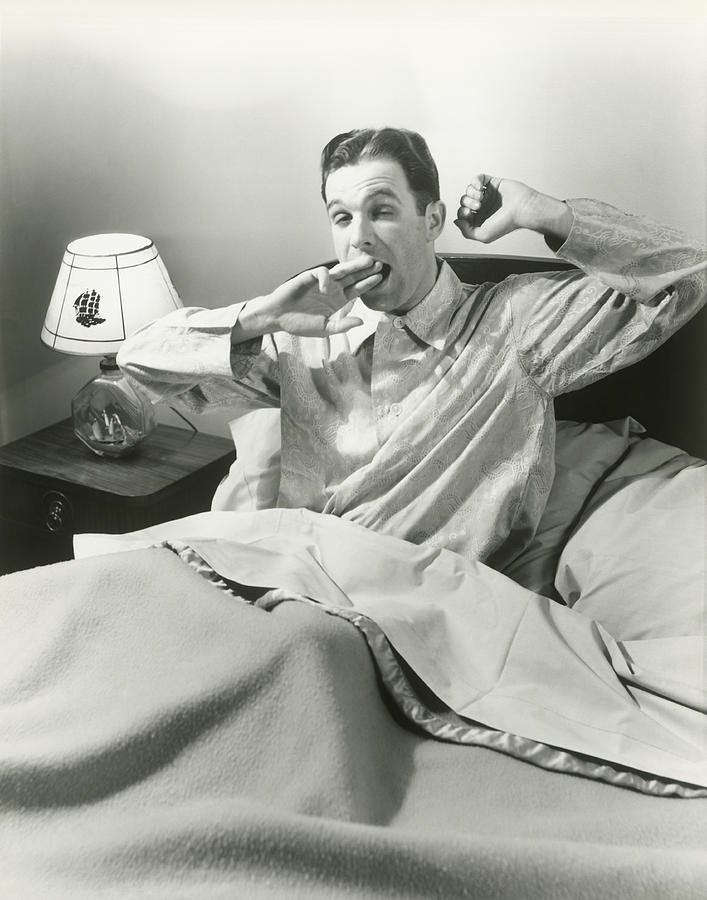 Adult Photograph - Mature Man Yawning Sitting In Bed by George Marks
