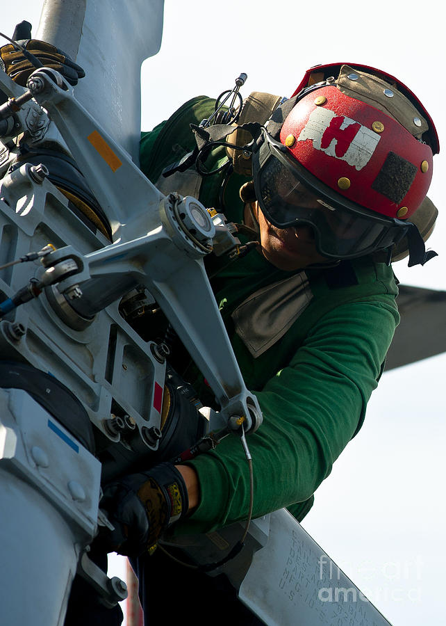 Safety Glass Photograph - Mechanic Inspects An Mh-60r Sea Hawk by Stocktrek Images