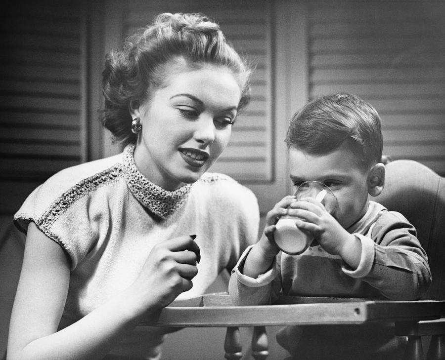 Child Photograph - Mother Assisting Son (2-3) Drinking Milk, (b&w) by George Marks