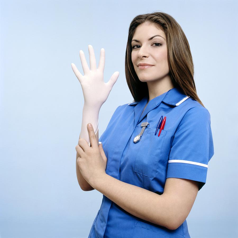 Blue Photograph - Nurse Pulling On A Glove by Kevin Curtis