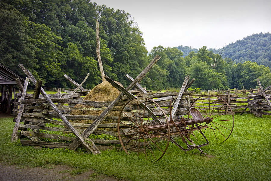 Old farm machinery and split rail fence on a in the