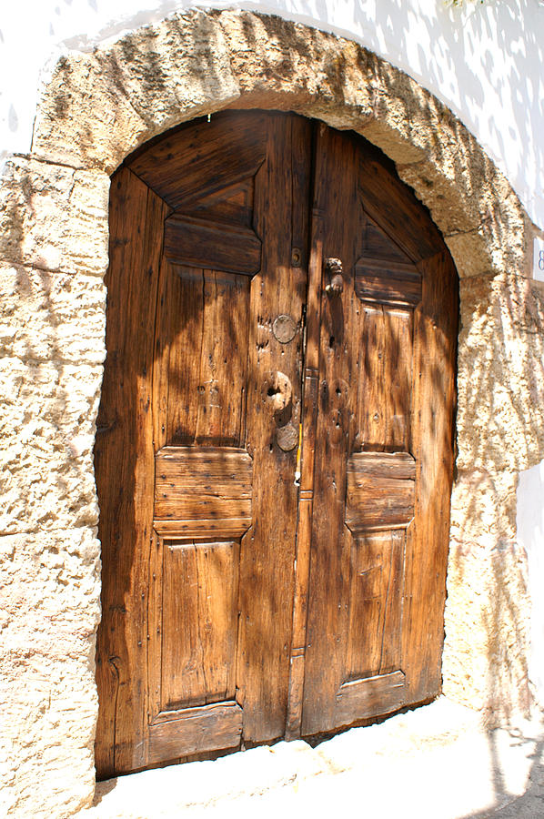 Old wooden door in a stone frame in lindos photograph by for Wooden back door and frame