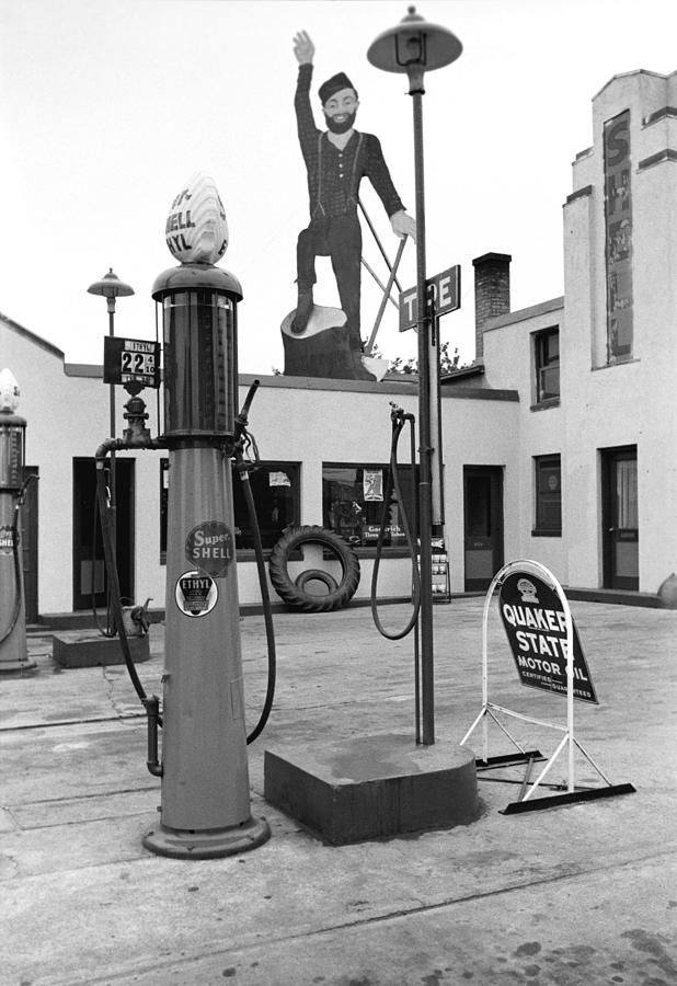 1930s Candid Photograph - Paul Bunyan Atop Gas Station, Bemidji by Everett