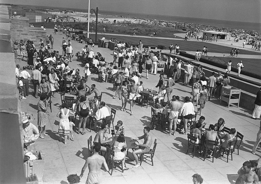 Adult Photograph - People Sitting At Tables By Beach, (b&w), Elevated View by George Marks