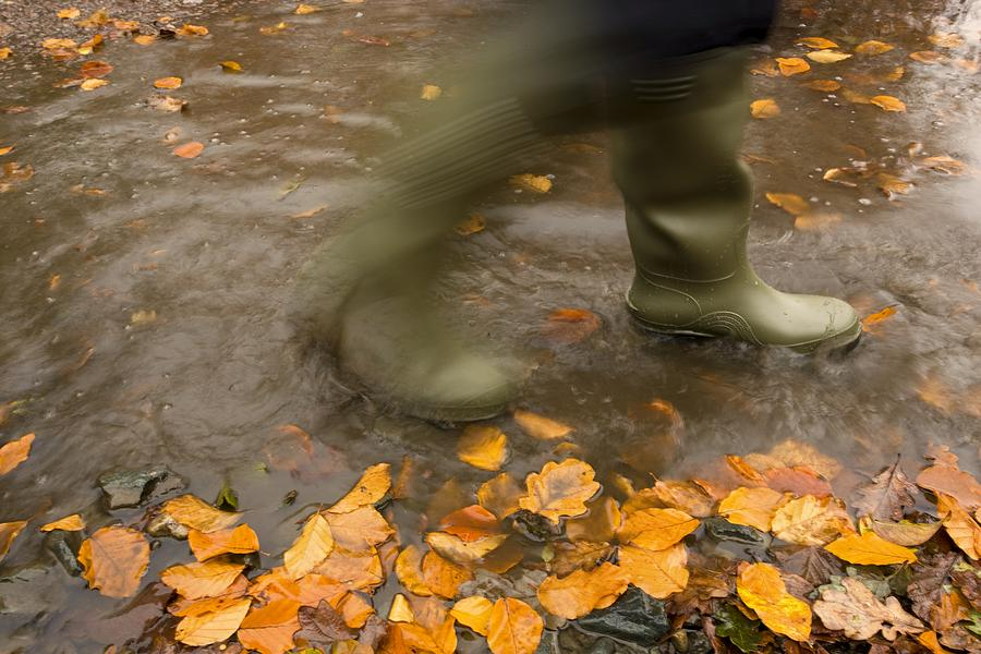 Boots Photograph - Person In Motion Walks Through Puddle by John Short