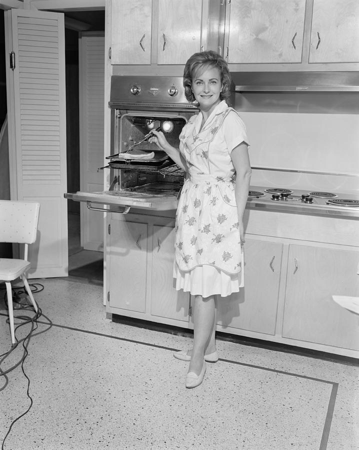 Adult Photograph - Portrait Of Woman Cooking In Kitchen by George Marks