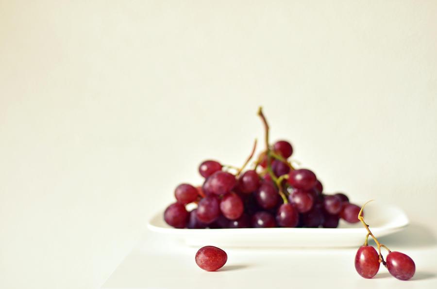 Horizontal Photograph - Red Grapes On White Plate by Photo by Ira Heuvelman-Dobrolyubova