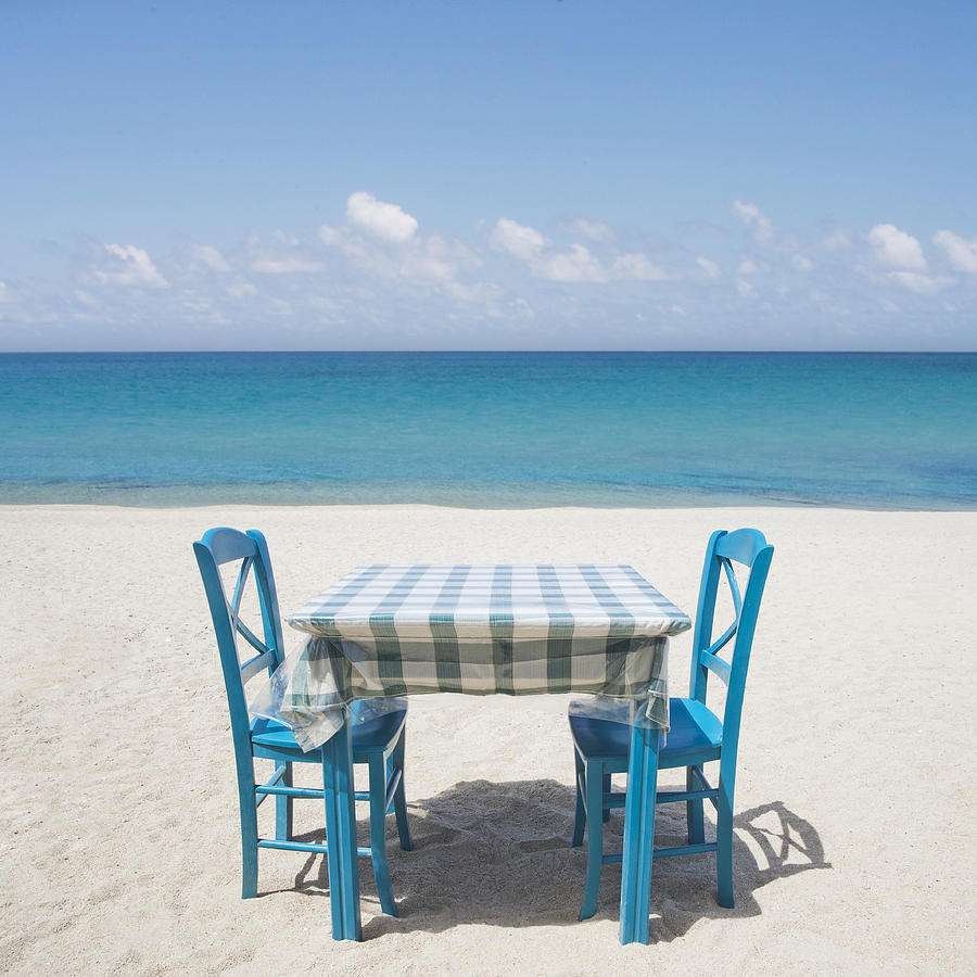 Restaurant table and chairs on beach in greece photograph for On the table restaurant