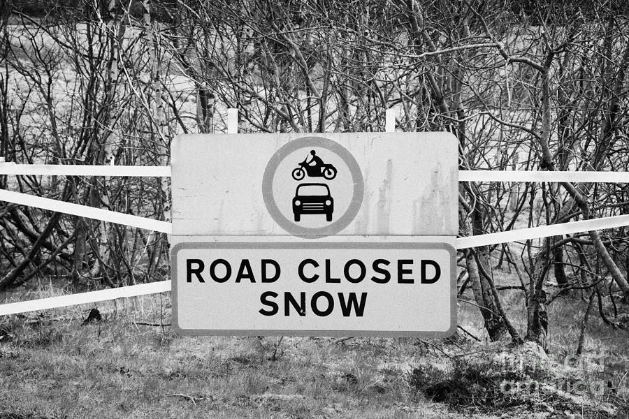 Road closed due to snow roadsign and barrier on the a in