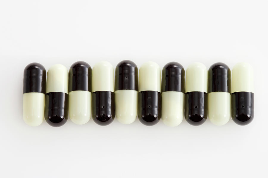Horizontal Photograph - Row Of Black And White Pills by Schedivy Pictures Inc.