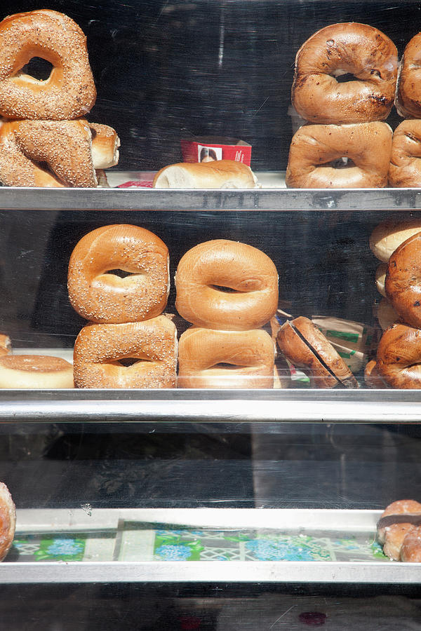 Vertical Photograph - Selection Of Bagels On Shelves Behind A Shop Window by Paul Hudson