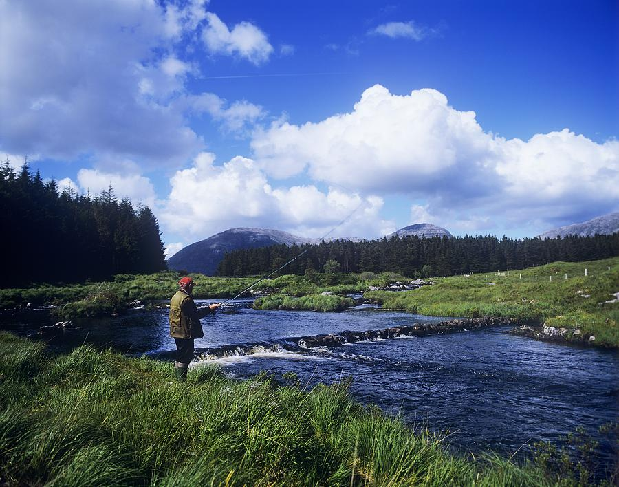 Connemara National Park Photograph - Side Profile Of A Man Fly-fishing In A by The Irish Image Collection
