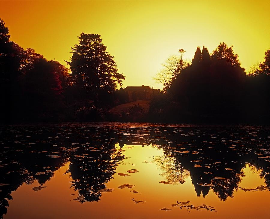 Attractions Photograph - Silhouetted Home And Trees Near Water by The Irish Image Collection